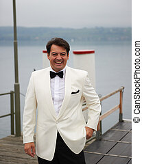 Smiling Groom On Pier - A smiling groom is standing on a...