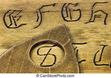 talking board - planchette on wooden talking board