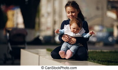 Little cute girl hugging her sister baby-girl in the park at sunshine day.