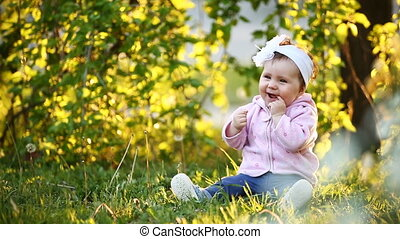 Little pretty baby-girl sitting on green grass in the park...