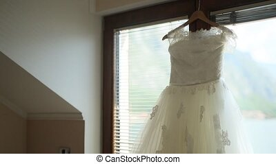 The bride's dress hangs on the cornice on window. - The...