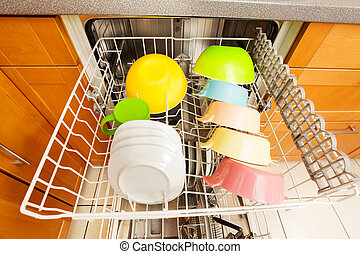 Dishwasher with clean utensils drying in it's rack -...