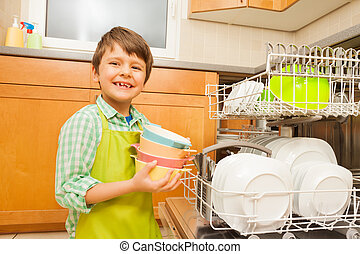 Smiling boy pulling out bowls of the dishwasher - Portrait...