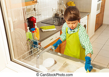 Boy in apron and rubber gloves doing the dishes - Portrait...