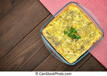 Quiche lorraine in square baking form on wooden background,...