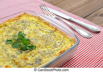 Quiche lorraine in square baking form on wooden background
