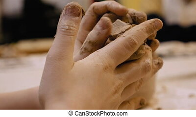 Sculptor is pugging clay for creating pottery - Female...