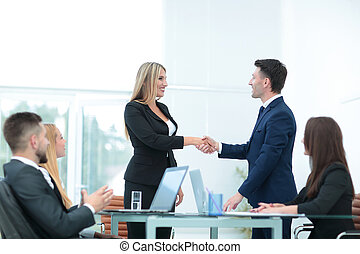 Handshake business partners after discussing the terms of...