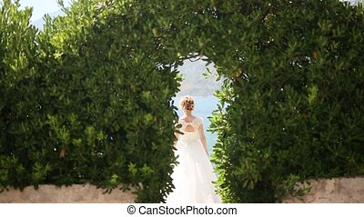 Bride in an arch of leaves. Wedding in Montenegro