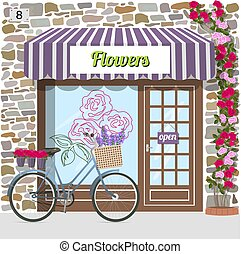 Flower shop building facade of stone. Bicycle with flowers...