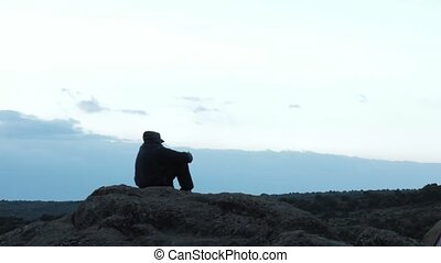 Lonely man looking into the distance to the mountains