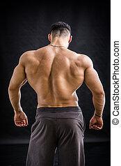 Handsome bodybuilder doing biceps pose - Handsome...