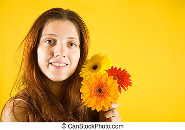 girl with flowers over yellow background