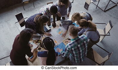 Brainstorming if creative mixed race group of people at modern office. Top view of group of people standing near table.