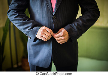correct button on jacket, hands close-up, dressing, man's...