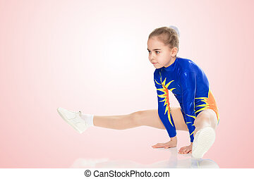 A girl gymnast performs a stand on her hands.