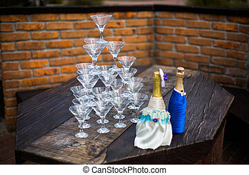 empty wine glasses are in the shape of a pyramid, decorated with bottles of champagne, wedding ceremony