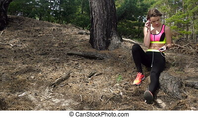 Sports girl listens to music in the forest