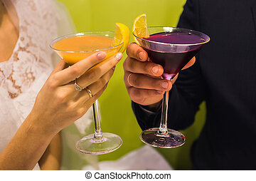 bride and groom holding glasses with cocktails, orange and...