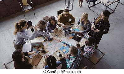 Top view of business team working at trendy loft office....