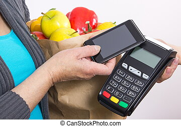 Hand of senior woman using payment terminal with mobile phone, paying for shopping