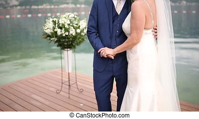Newlyweds hold hands on the sea. Couple holding hands....