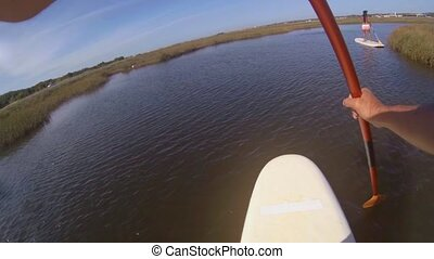 Chest POV of man stand up paddleboarding on lake. Young man...