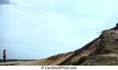 girl walks on top of a Sandy Hill at daytime
