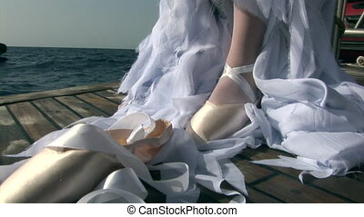 Model in costume of angel clothes pointe shoes on ship near water in Red Sea.