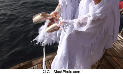 Model in white costume of angel clothes pointes on ship near water in Red Sea.