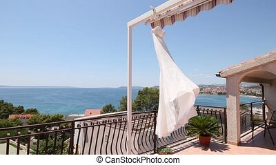 The bride's dress flutters in the wind on the balcony,...
