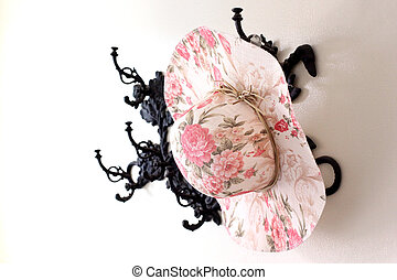vintage woman straw hat hanging on a hat-rack