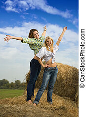 Two girls standing on hay bail at farmland