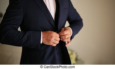 The groom zips up the jacket. Groom wedding dress