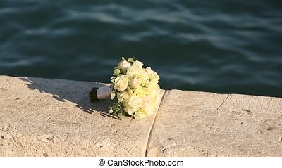 Bridal bouquet of roses and eucalyptus on a sea berth....