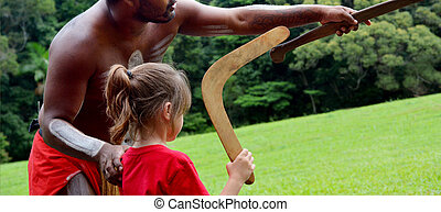 Australians aboriginals man teaches a young girl how to...