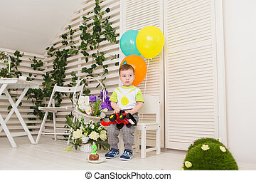 Child, birthday party and childhood concept - Little boy with a balloons and toys indoors