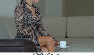Young peaceful woman sitting on couch and drinking tea...