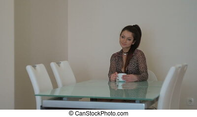 Young peaceful woman sitting on chair and drinking tea...