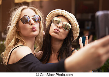 Blonde and dark hair girls taking a selfie