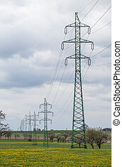 High voltage power lines above spring meadow. Electricity poles on sky background.