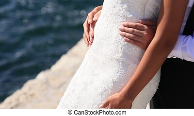 The groom embraces the bride on the beach. Wedding in Montenegro