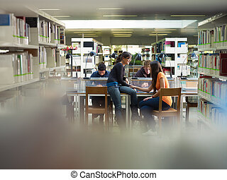 students in library - group of college students studying in...