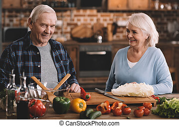 portrait of cheerful senior couple resting while making salad at home