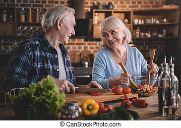 Happy senior couple cooking vegetable salad together
