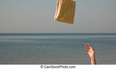 Hand throwing towel, sea background. Flip flop and beach...