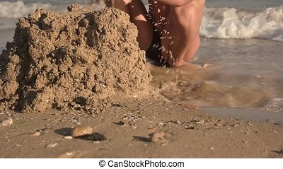 Boy is playing with sand. - Kid on seashore, slow-mo. Boy is...