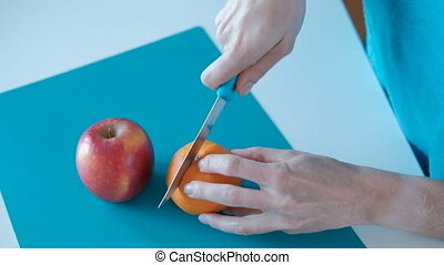 Woman cuts fresh orange with knife on the board at home....