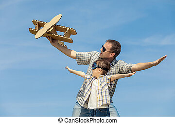 Father and son playing with cardboard toy airplane in the...