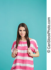 young beautiful smiling woman with long hair in pink shirt on blue background.